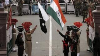 Pakistani rangers (wearing black uniforms) and Indian Border Security Force (BSF) officers lower their national flags during a daily parade at the Pakistan-India joint check-post at Wagah border near Lahore, Pakistan
