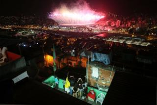 Personas en el patio de una casa en un favela viendo desde lo alto los fuegos artificiales en el Estadio Maracaná