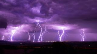Photograph shows deep purple sky with flashes of several flashes of flightening