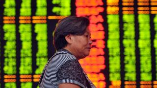 Investor in front of share price screens in China