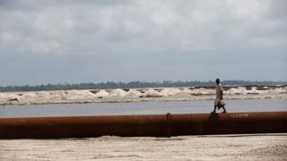 "A man walks on a pipeline running through the proposed Dangote oil refinery site near Akodo beach in the outskirt of Nigeria""s commercial capital Lagos June 25, 2016."