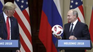 Путин держит мяч с улыбкой, Трамп смотрит на него вопросительно