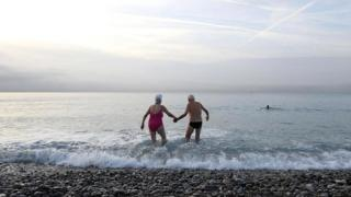 Пожилые мужчина и женщина входят в море