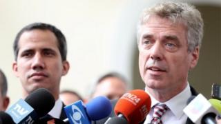 German ambassador to Venezuela, Daniel Martin Kriener (R), speaks to the media as he arrives with Venezuela's self-proclaimed interim president Juan Guaido