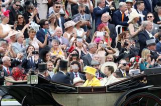 Люди фотографують приїзд королівської родини на перегони в Аскоті.