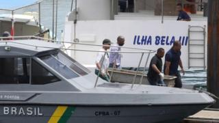 The body of one of the victims of a boat wreck, after a ferry sank off the north-eastern state of Bahia, is loaded at the Maritime Terminal of Salvador, Bahia State, on August 24, 2017.