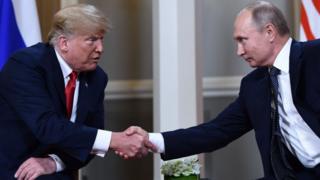 Trump y Putin se dan la mano.