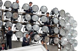 Cameramen take up position on a building in Pyongyang, North Korea, during a mass rally and parade