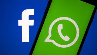 The Facebook and WhatsApp logos are seen on a phone in this photo illustration