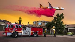 A plane drops fire retardant behind homes along McVicker Canyon Park Road in Lake Elsinore in the US