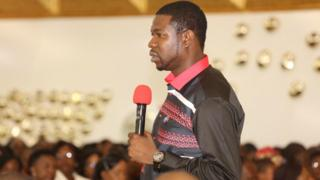 Walter Magaya speaks to a congregation whose faces are blurred
