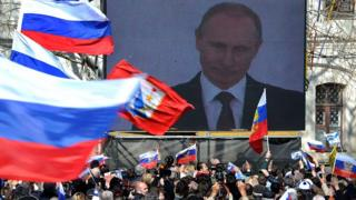 Putin on a big screen announcing the annexation of Crimea