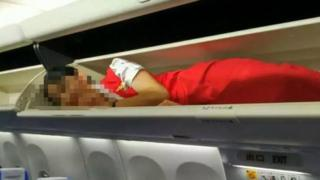 This photo seen on the WeChat account of the 'Civil Aviation Tabloid' channel, shows an air stewardess lying in an overhead luggage compartment