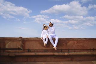 Fondaki gökyüzünün önünde oturan baba oğul