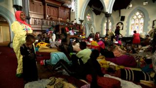 People and their belongings inside the church