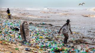 A man collects recyclable material at the polluted Korle Gono beach