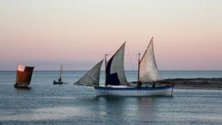 A schooner sails from the coast at dusk