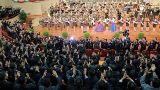 North Korean leader Kim Jong-un, centre, waves during a celebration, surrounded by high-ranking military officials and nuclear scientists. In the background, an orchestra and row of standing women can be seen on stage