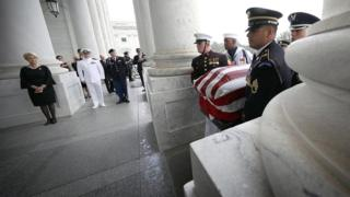 John McCain's widow Cindy McCain and his sons Jack (C) and James (R) watch joint service members of a military casket team carry the casket of Senator John McCain into the US Capitol in Washington DC on 31 August 2018