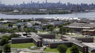 The Rikers Island jail complex stands in the foreground with the New York skyline in the background.