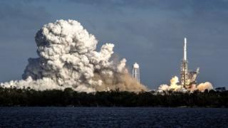 The space rocket is seen launching, surrounded by plumes of smoke at its base