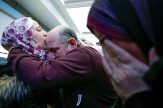 "Syrian refugee Baraa Haj Khalaf kisses her father Khaled as her mother Fattoum (R) cries after arriving at O""Hare International Airport in Chicago, Illinois,"
