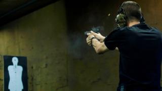 Brazilian reserve militaryman Rildo Anjos shoots at a target