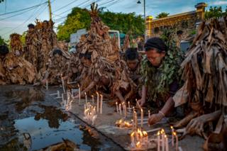 in_pictures Devotees covered in mud and dried banana leaves light candles and pray outside a closed church