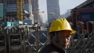 Pekerja Cina berdiri di depan lokasi pembangunan di Beijing, 16 Desember 2016.