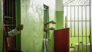 Prisoners use mirrors to watch visitors from their cells in the aging penitentiary of Desembargador Raimundo Vidal Pessoa, opened in 1904, on February 17, 2016, in Manaus, Brazil.