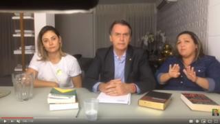 Reprodução de transmissão ao vivo feita por Bolsonaro, em que aparece ao lado da esposa e de intérprete de libras