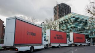 The three vans with the billboards parked in Kensington with the fire-damaged Grenfell Tower in the background