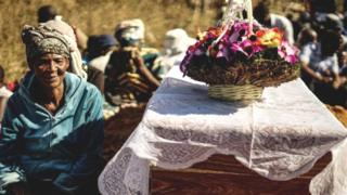 The mother of Ishmael Kumire, 42, sits next to her son's coffin during his funeral ceremony after he was shot during post-election violence on August 1 in Harare, at his homestead in Chinamhora village, Domboshava, outside Harare, on August 4, 2018