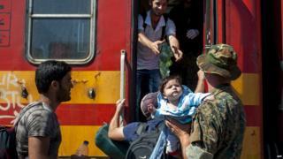 Migrants board train at Gevgelija, Macedonia, 23 August 2015