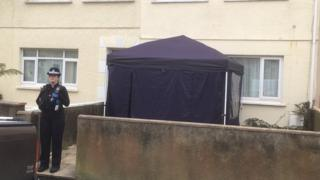 A police officer stood outside a forensics tent which has been placed outside a house on Lakeview Place