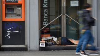Una persona sin hogar descansa en la puerta de un banco de Barcelona