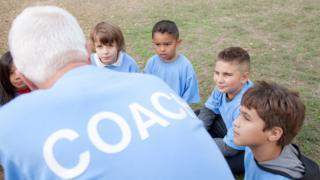 Coach talks to children (actors)