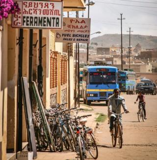A man on a bicycle riding past a bike repair shop in Asmara, Eritrea