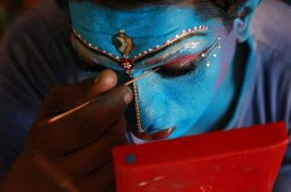 A man gets ready backstage before performing in the Cochin Carnival.