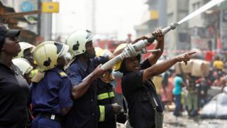 Firefighters holding a water hose in Lagos, Nigeria - Wednesday 29 January 2020
