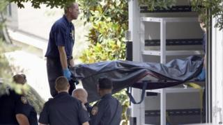 Officials remove a body from a house in Houston. Photo: 9 August 2015