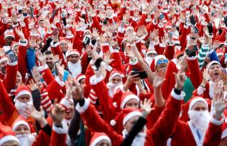 Competitors warm up ahead of the start of the London Santa Run, in Victoria Park