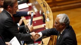 Portuguese PM Pedro Passos Coelho shakes hands with Socialist leader Antonio Costa
