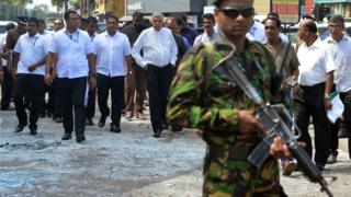 "Sri Lankan Prime Minister Ranil Wickremesinghe (C) arrives to visit the site of a bomb attack at St. Anthony""s Shrine"