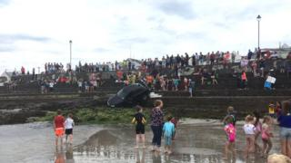 Lots of children and holidaymakers are pictured on steps surrounding a car that had gone over the edge toward the beach before becoming lodged on an angle.