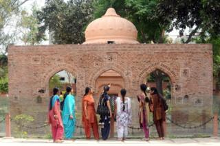 Indian visitors look at the bullet ridden wall at the historical site of the Jallianwala Bagh massacre in Amritsar on April 12, 2011
