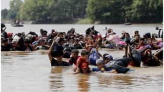 Migrants, mostly Hondurans, cross the Suchiate river, which separates Guatemala and Mexico, on 29 October 2018