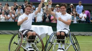 Gordon and his partner Alfie Hewett lift the trophy for the men's wheelchair doubles at Wimbledon