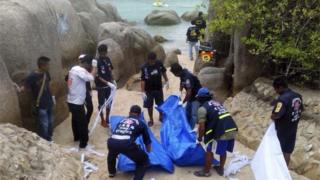 Thai workers carry the bodies of the two murdered British tourists on Koh Tao island
