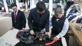 Miembros de la iglesia inspeccionan un AR-15
